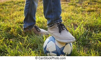 the guy rested one foot on a soccer ball
