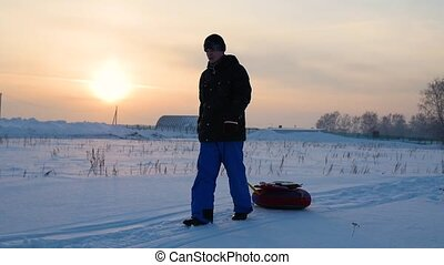 the guy rises to snowy hill with snowtube.slow motion. snow winter landscape. Sunset time