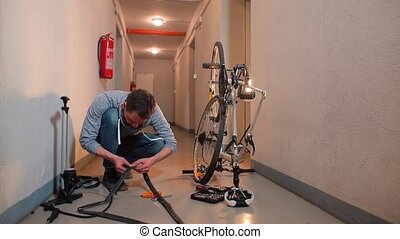 The guy seals a hole in the rubber of a bicycle wheel