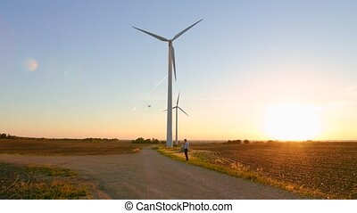 The guy starts the drone against the background of the windmills.