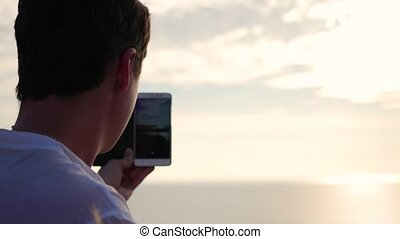 the guy takes a photo of the sunset panorama