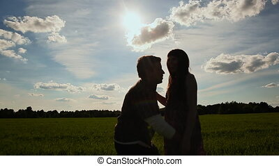 The guy turns the girl against the sun. Silhouettes of love couple.