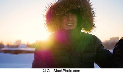 the guy waving his hand and laughing merrily in the winter, at sunset. snow winter landscape. outdoors
