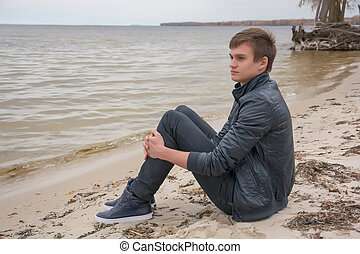 The guy who is sitting on the shore of the sea of autumn