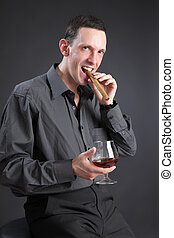 The guy with a cigar and cognac on a black background