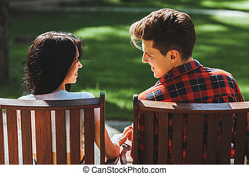 The guy with the girl sitting on chairs and holding hands looking into each other's eyes at sunset. The concept of pure love, happiness, peace and relaxation. Beautiful young couple during a romantic date.