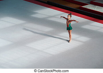 The gymnast is in the initial position, hands to the side