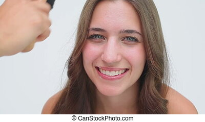 The hair of a smiling woman being brushed