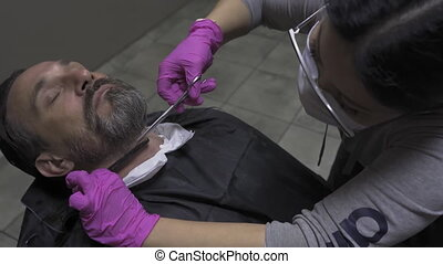The hairdresser cuts the beard to the client by cutting or ...