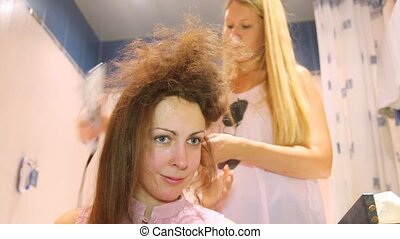 The hairdresser does a hairdress to young woman - The...