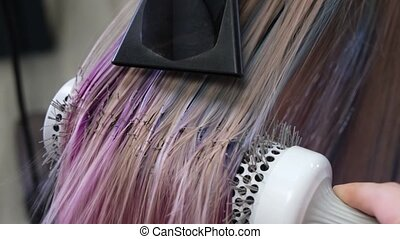 The hairdresser dries the blond hair of the client after dyeing it blue and red