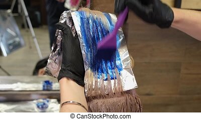 The hairdresser dyes the client's blond hair blue and red. Paint application process