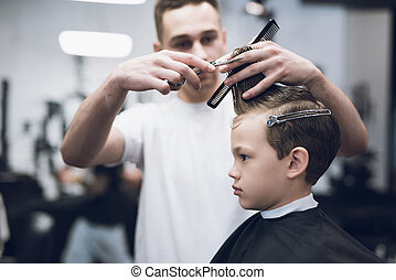 The hairdresser makes a fashionable pretty hairstyle for the boy in a modern barbershop.
