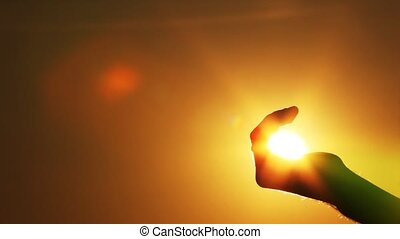 the hand catches the sun in a fist