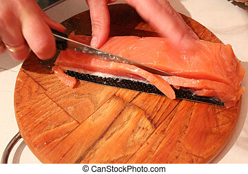 The hand cuts slices of a red fish