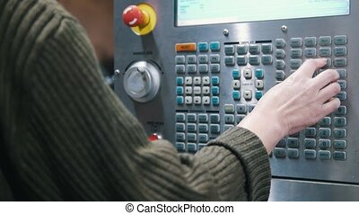 The hand enters data on the control panel of the lathe