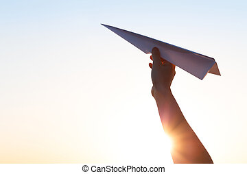 The hand hold paper airplane and launch against the background of the bright sun