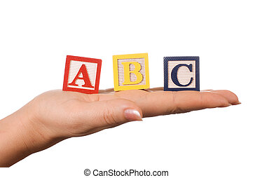 The hand holds a cube with letters