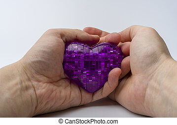 The hand holds the heart on a white plastic background.