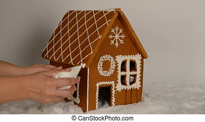 The hand-made eatable gingerbread house, adding by hand of icing on roof and snow decoration