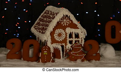 The hand-made eatable gingerbread house, adding by hand of...