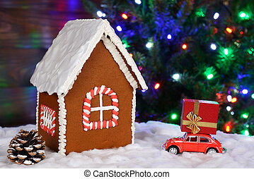 The hand-made eatable gingerbread house, snow decoration, car with gift and New Year Tree with garland in background