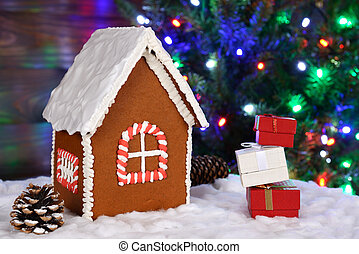The hand-made eatable gingerbread house, snow decoration, gifts and New Year Tree with garland in background