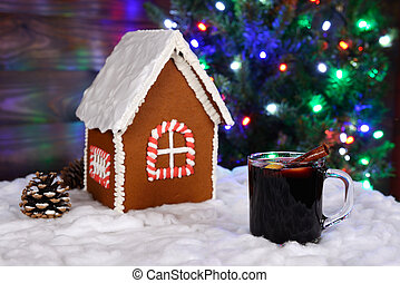 The hand-made eatable gingerbread house, snow decoration, hot wine and New Year Tree with garland in background