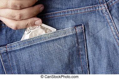 the hand of a man who takes a condom in the back pocket of his jeans