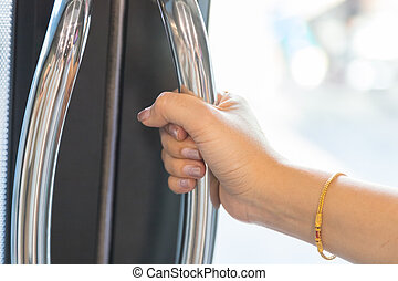 hand of a woman holding the door