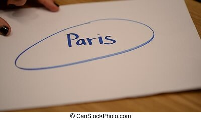 The hand of a young girl encircles the inscription Paris...