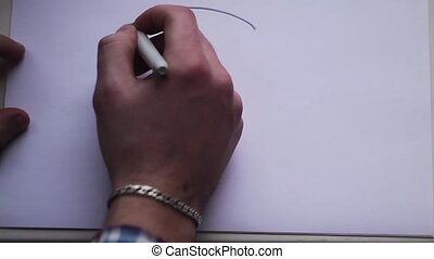 the hand of the man draws a smiley face on a white sheet of paper