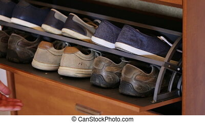 The hand opens closet with men's shoes. - The hand opens the...