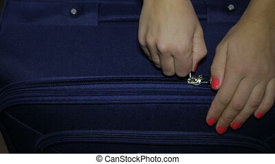 The hand pulls the zipper on the luggage - Woman closes the...