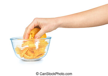 the hand takes a handful of potato chips from a transparent ...