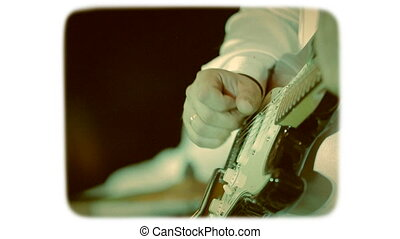 the hand touches the strings on an electric guitar. 8mm retro style film.