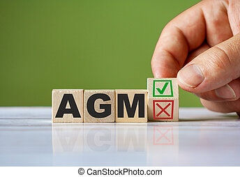 The hand turn wooden block with red reject X and green confirm tick as change concept of AGM. Word AGM conceptual symbol