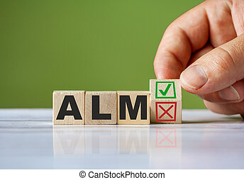 The hand turn wooden block with red reject X and green confirm tick as change concept of ALM. Word ALM conceptual symbol