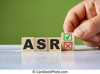 hand turn wooden block with red reject X and green confirm tick as change concept of ASR. Word ASR conceptual symbol.
