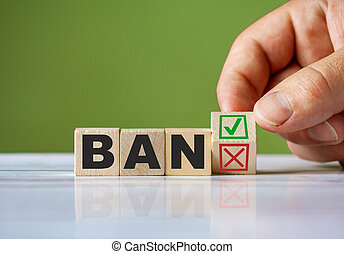 hand turn wooden block with red reject X and green confirm tick as change concept of BAN. Word BAN conceptual symbol.