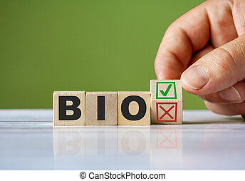 hand turn wooden block with red reject X and green confirm tick as change concept of BIO. Word BIO conceptual symbol.