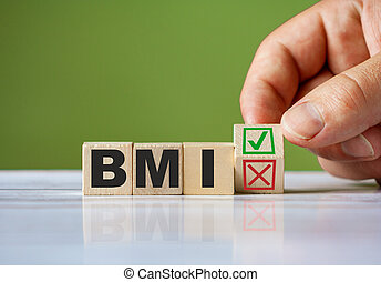 hand turn wooden block with red reject X and green confirm tick as change concept of BMI. Word BMI conceptual symbol.
