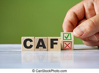 hand turn wooden block with red reject X and green confirm tick as change concept of CAF. Word CAF conceptual symbol.