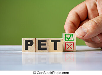 hand turn wooden block with red reject X and green confirm tick as change concept of PET. Word PET conceptual symbol.