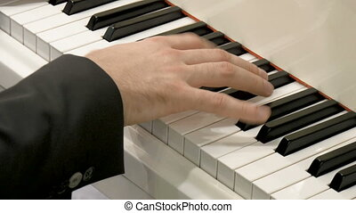 The hands of a classical pianist on the piano. Close-up.