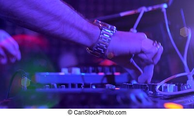 The hands of a DJ performing in a nightclub at a party. Neon lights and disco lights