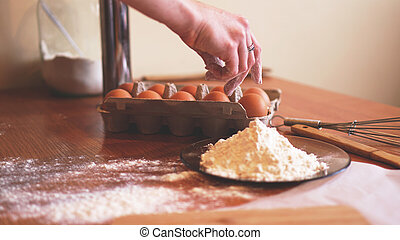 The hands of a female chef picking an egg for making dough while making bread