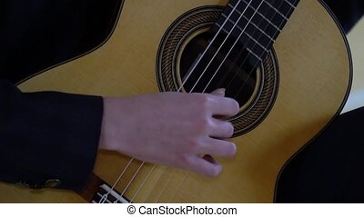 The hands of a young man fingering the strings of a classical guitar