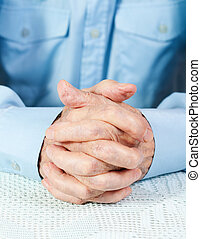 the hands of elderly man are crossed