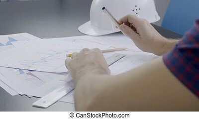 The hands of male architect who is completing the blueprint of the building in his office.